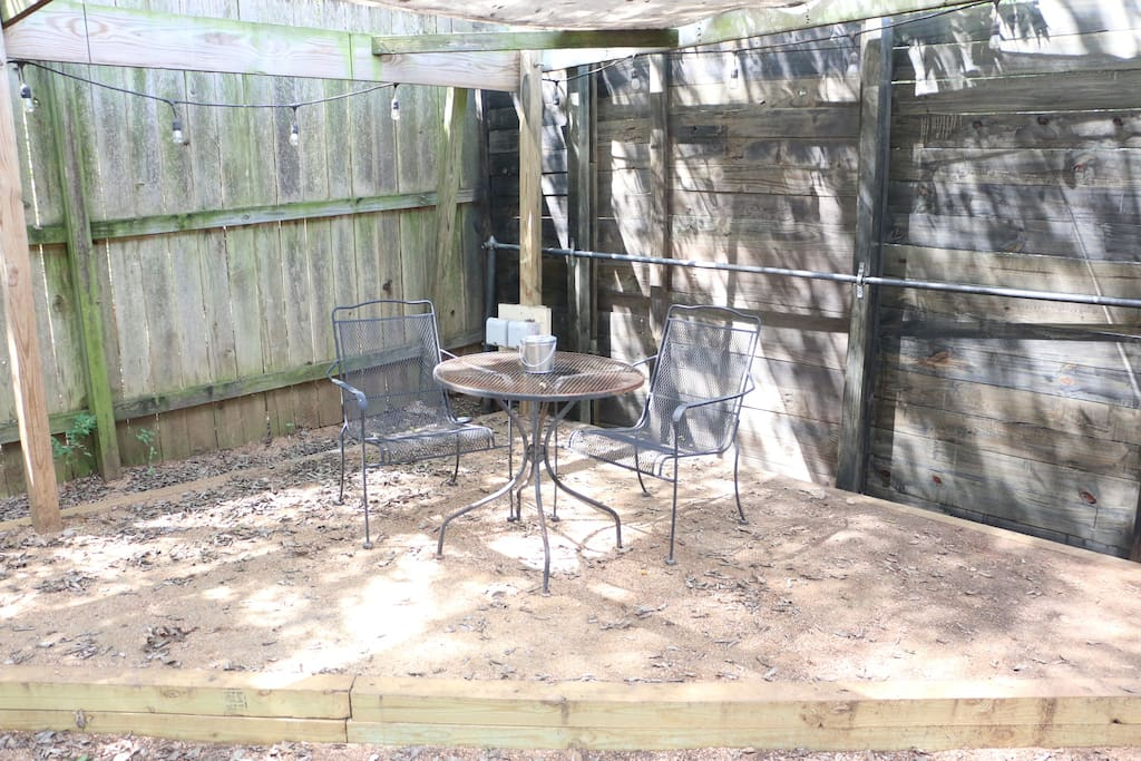 Enjoy your own covered backyard space with outdoor lighting and patio table.