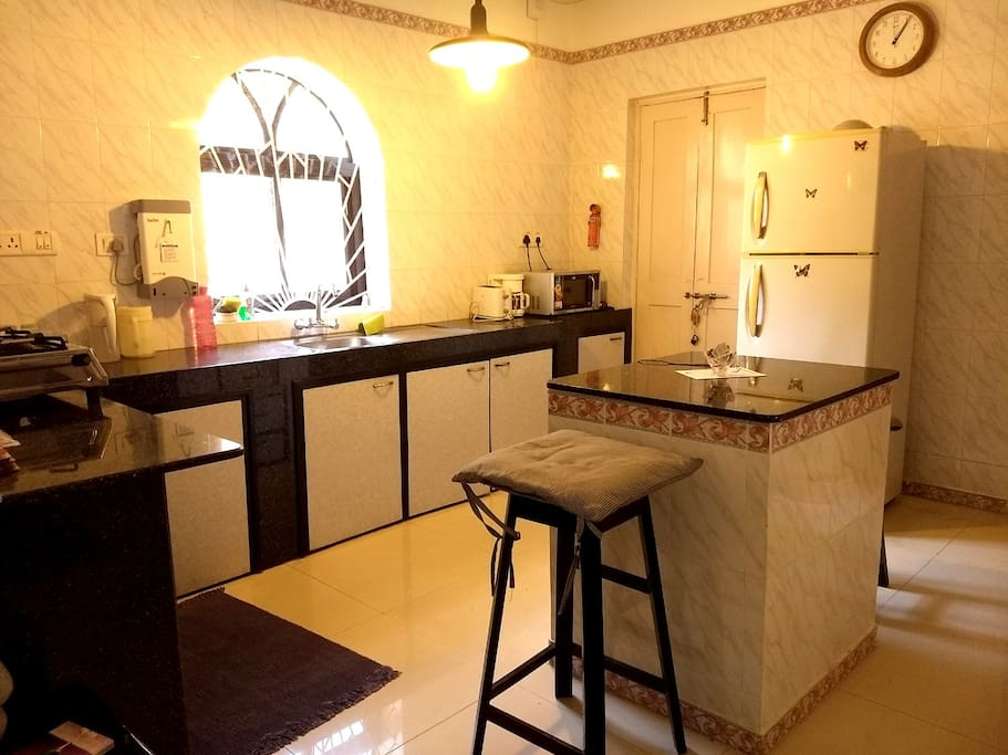 Common kitchen with stove, microwave, fridge, water, utensils and other amenities