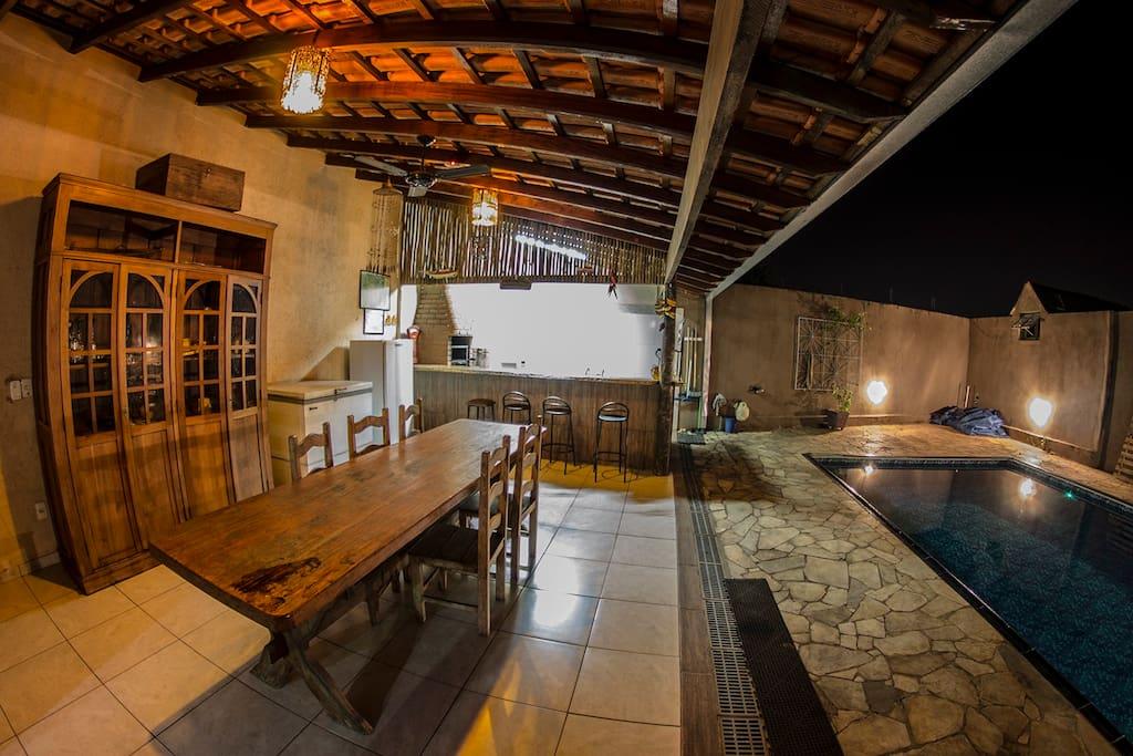 Mesa para refeições, cozinha ao fundo e à direita a piscina