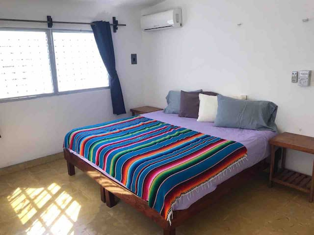 King bedroom with AC and fan. Dresser and ample hanging space for clothes also in the bedroom.