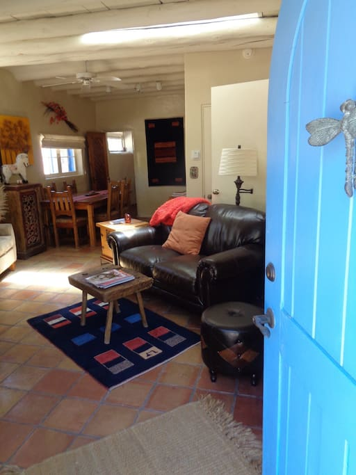 The bright blue front door, very typical throughout Santa Fe and also Taos, opens into the cozy living room area.