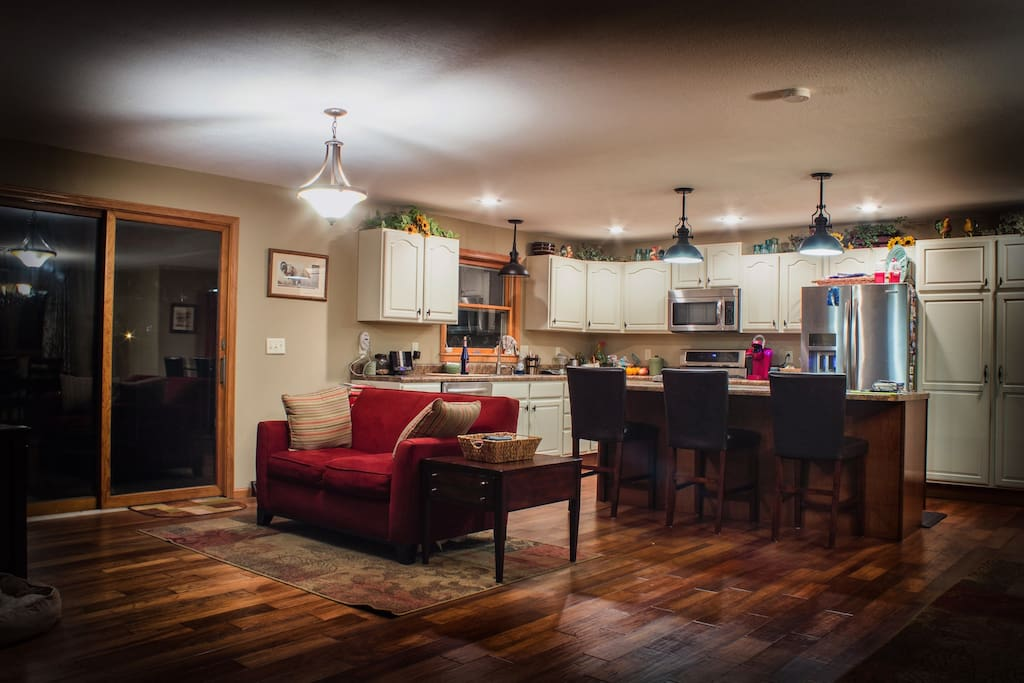 Open concept living room, dining area, with well equipped kitchen.