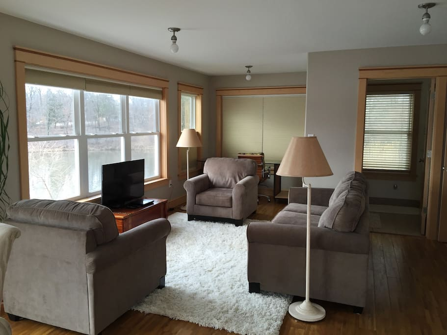 Living room/ Kitchen/ Dining has views of Walton Lake in 3 directions.  HD TV, BlueRay player, desk in background.