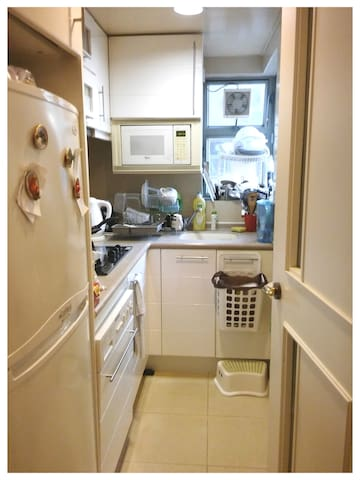 Kitchen View from Main Hallway. Fridge, Microwave, Gas Stove, Sink and all Cutleries / Plates / Pans Free for Guests to Use.