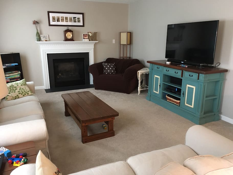 Living room with fireplace, TV, and room to gather