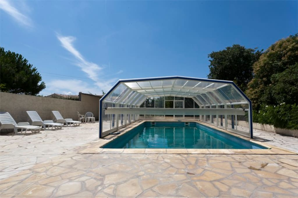 Swimming pool with retractable cover to keep water warm at extremes of season