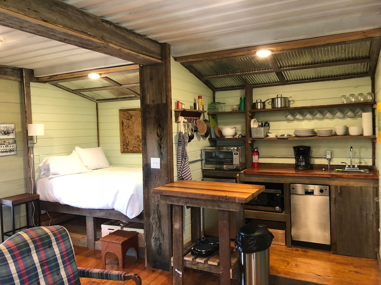 The container doors were welded open to create two extra spaces. The berth style bed on the left, and a mini kitchen on right—with convection oven, mini fridge, dishwasher and microwave. The shelves and trim are reclaimed cypress.