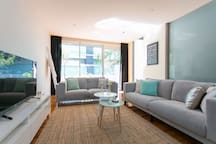 "Spacious and bright lounge area with a 55"" LCD Smart TV - glass sliding doors lead out to the balcony"