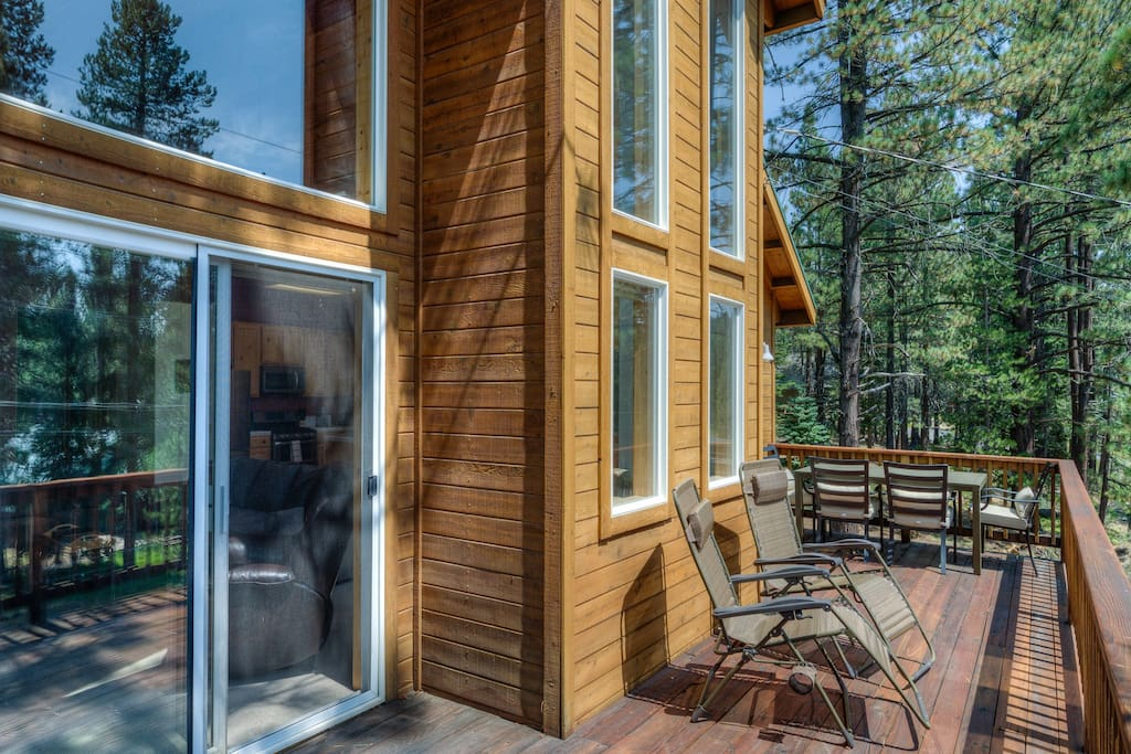 Tall pine trees surround the deck.