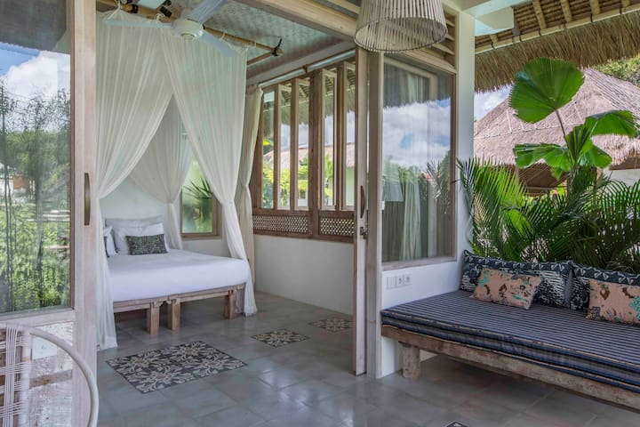 View to carved antique Javanese panel and glorious daybed on patio. Camellia 1 is normally set up as a double.