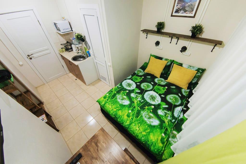 Кровать, общий вид студии, мини-кухня.