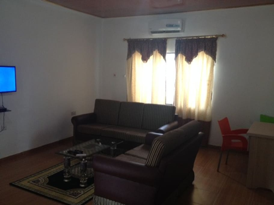 spacious living room with couches, satellite TV, and AC unit