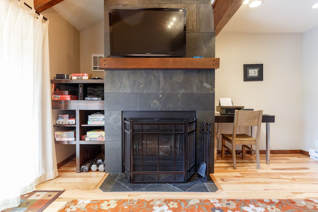 "Updated family room with slate wood burning fireplace. 48"" TV mounted above fireplace mantle."