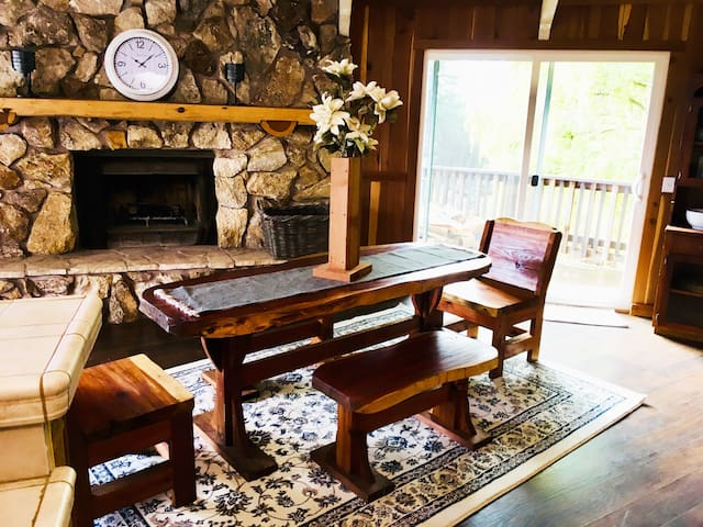 Dining area with custom handcrafted redwood slab table and benches. Wood for fire available by request.