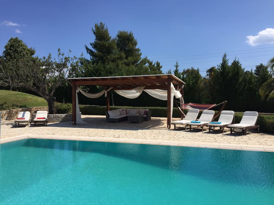 around the pool, pool patio with comfortable patio furniture , swing - hammock and 6 chairs to enjoy the Greek sun.