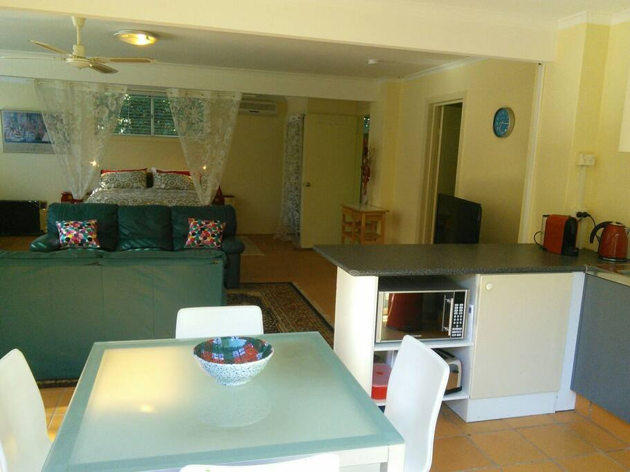 Open space area showing queen bed, lounge, TV, dining and kitchenette