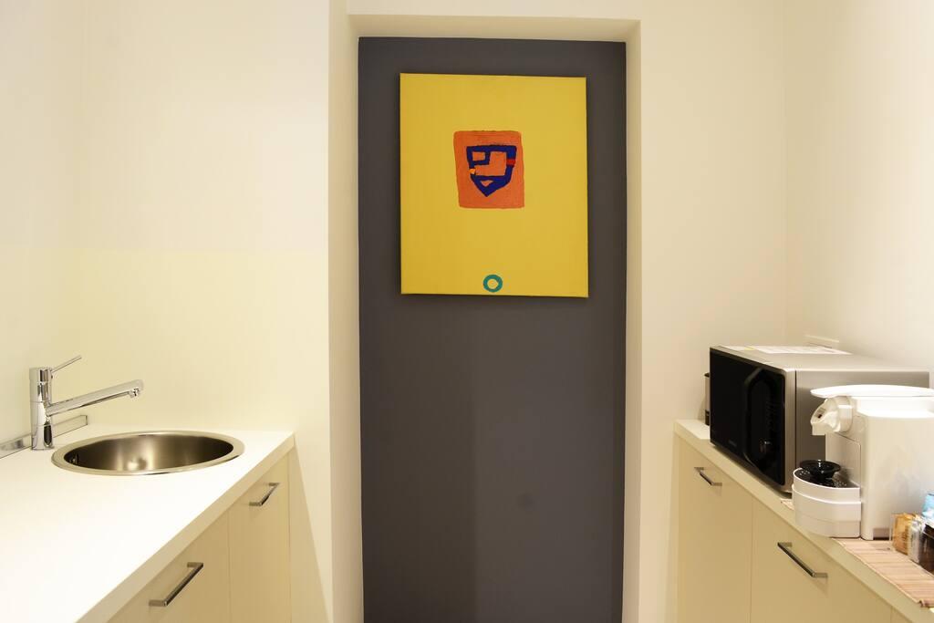 Zona Cucina attrezzata con Forno a microonde, macchina del caffè, bollitore, piastra a induzione Opera di Nicholas Howey