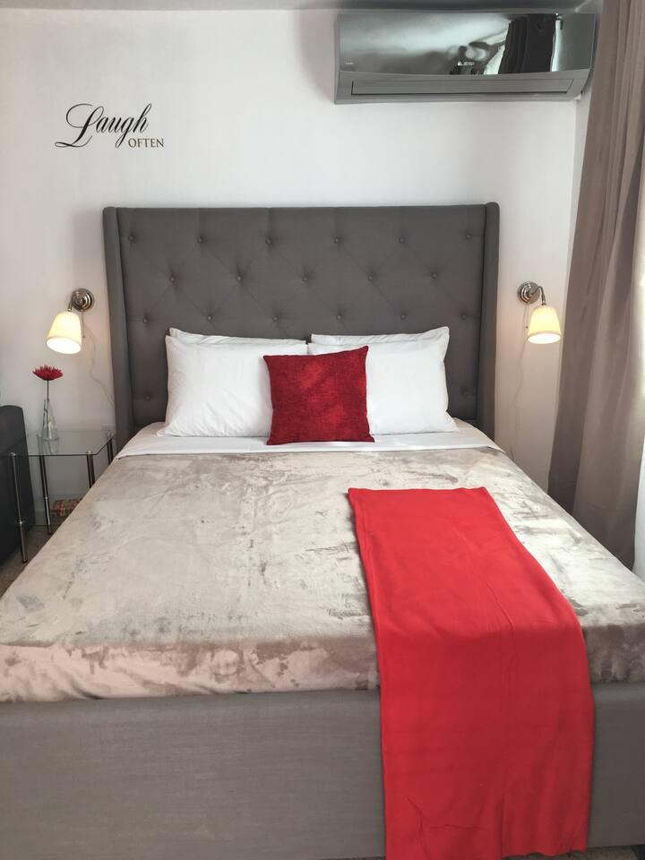 Vista al área de dormitorio. Tiene una cama Queen size que le permite acomodar fácilmente dos personas; en adición a lo anterior, contamos con aire acondicionado en la habitación.
