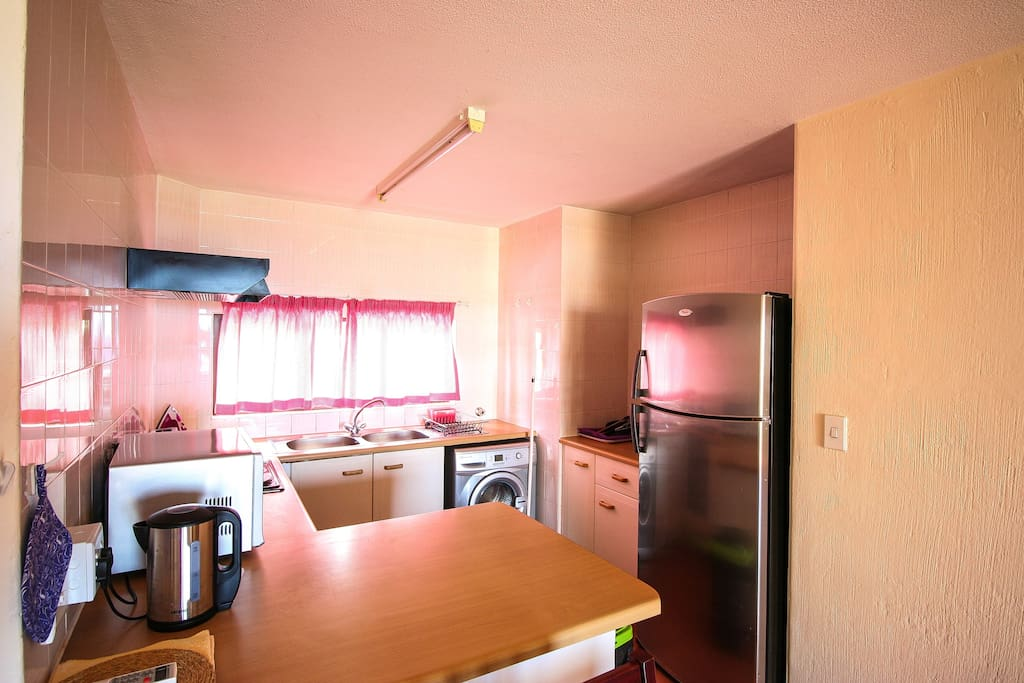 Kitchen with microwave, oven, fridge, kettle, toaster and kitchenware.