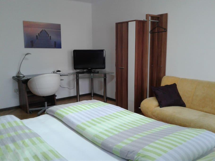 Zimmer mit bequemen Doppelbett, TV, Sofa, Schreibtisch, Kasten