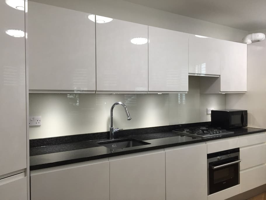 a new clean  and integrated kitchen with oven and microwave, laundry machine, fridge, etc.