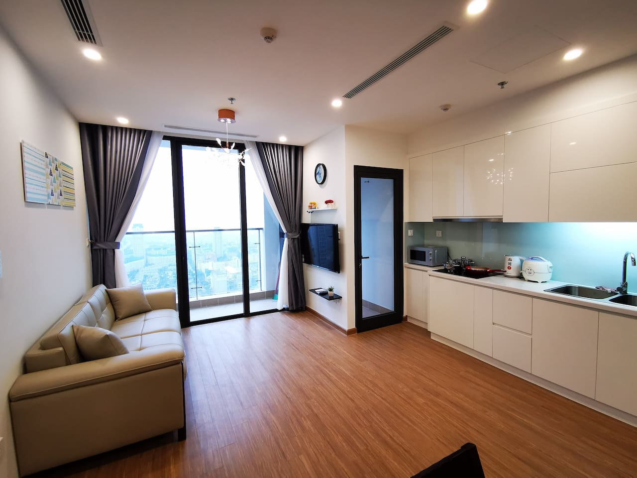 Living room has a large window and a balcony to enjoy the sunshine in daytime and sparkling building view at night. Wooden floor brings a cozy & classy style. The living room connects to kitchen (full kitchenette) and another entrance to the balcony.