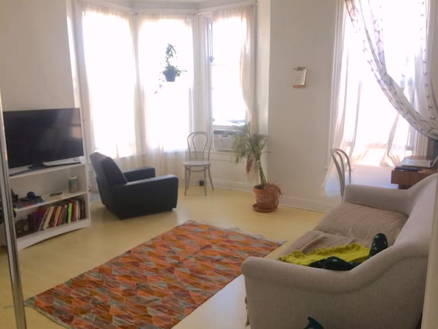 living room with tv (netflix, hulu, youtube) and small dest in the far corner, bay window with lots of light.