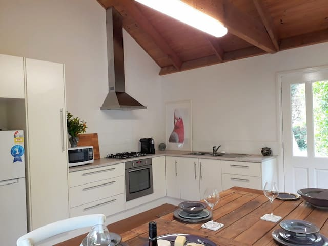 spacious kitchen with large rustic table and all the essentials, overlooking cottage gardens