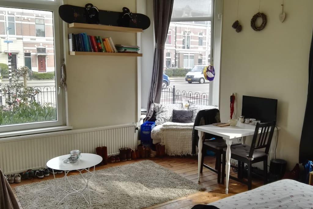 Grote openslaande ramen, comfortabel erkertje en tafel met tv