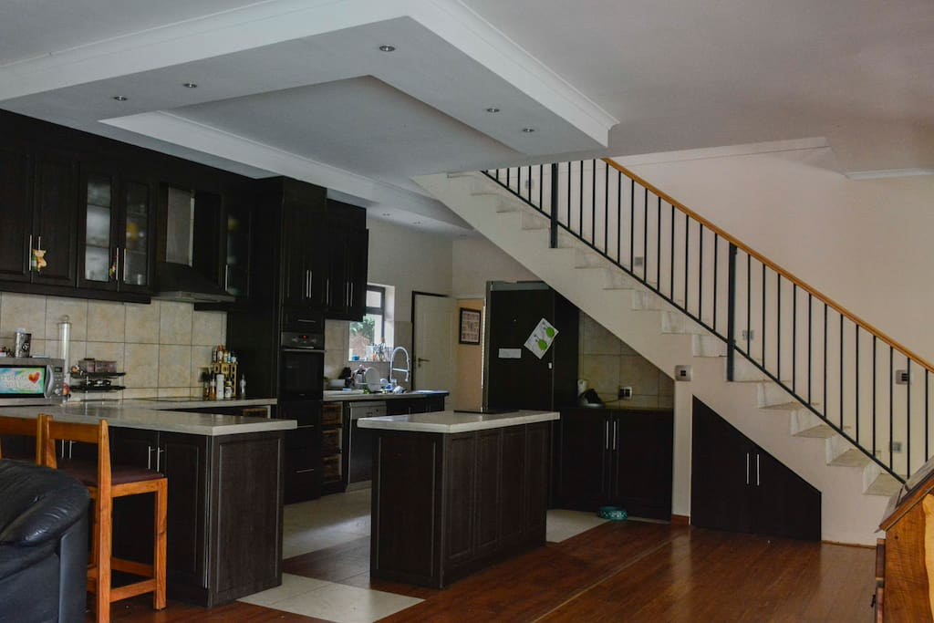 Open plan kitchen with stairs leading to 5 bedrooms upstairs and additional reception area with TV
