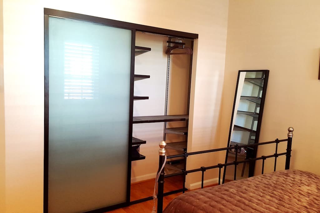 Large wall closet with hanging space, shelves and drawers.