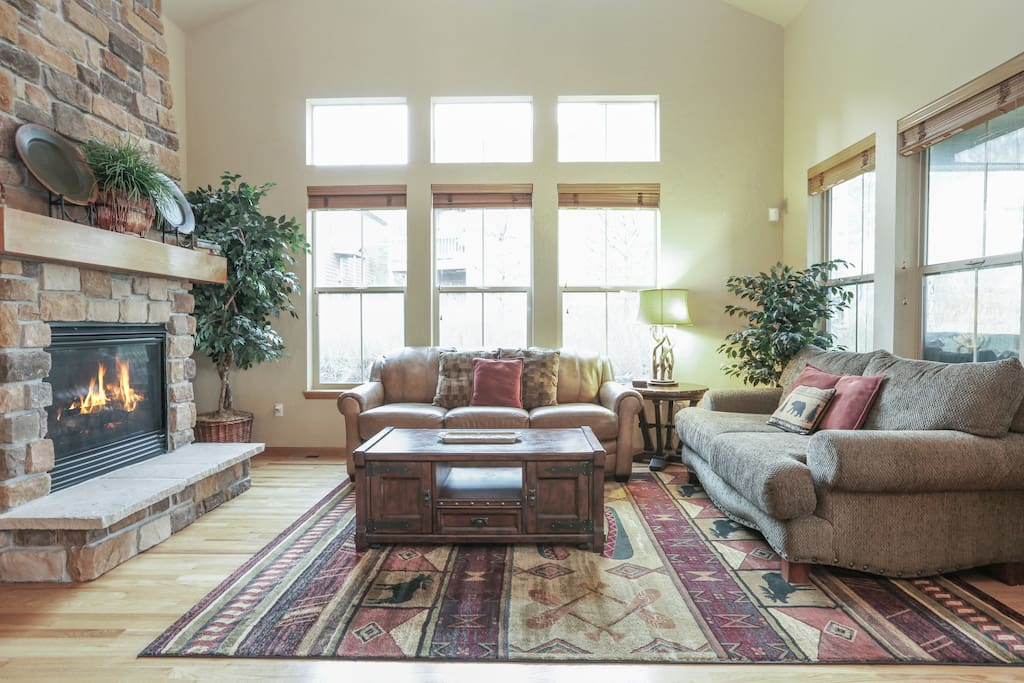 Stone fireplace, vaulted ceilings, sleeper sofa, and love seat in the living area.