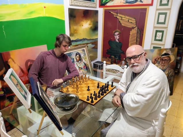 Una entretenida partida de ajedrez con un joven visitante de Airbnb en el salon del comedor.