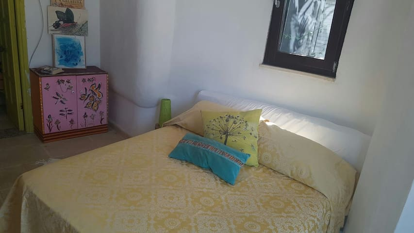 Il letto sotto una finestra con zanzariere