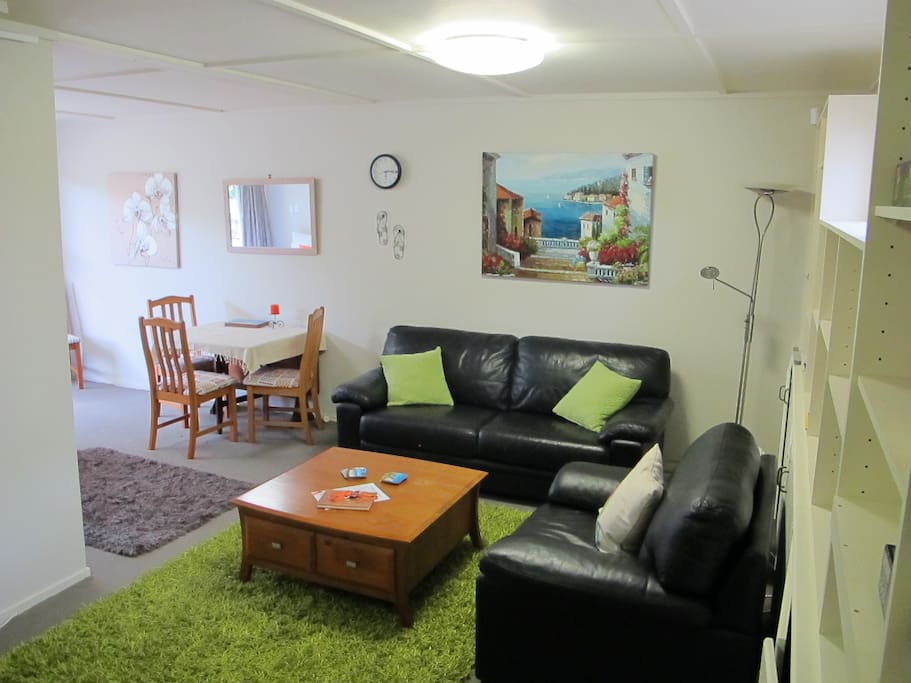 Living area with TV, couch, dining table & chairs & a double bed
