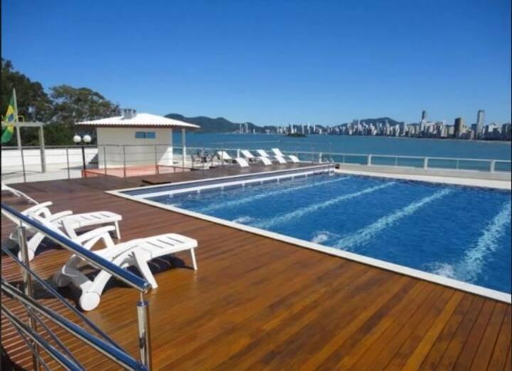 Home Office beira mar: prédio c piscina e garagem