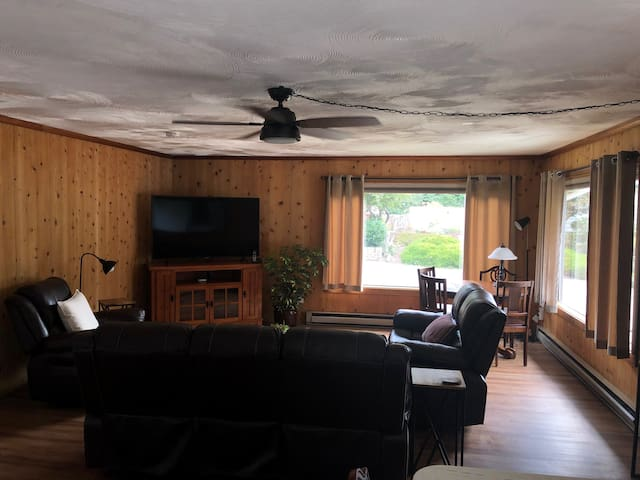 The living room features a 64 inch curved UHD TV with basic cable and netflix.