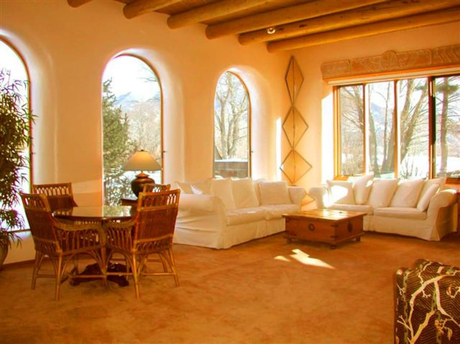 Large and spacious living room with arched window views to Taos mountain and window wall looking to acequia stream