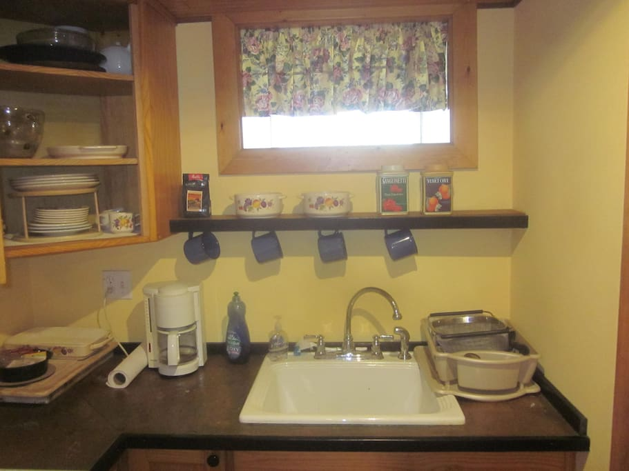 Kitchenette with deep sink, basic pantry supplies including tea and coffee, tableware, copper counter top