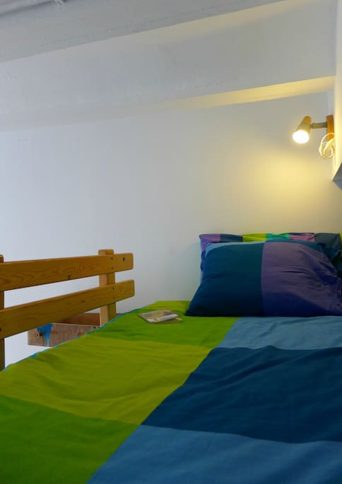The single bedroom has a large bed with reading light