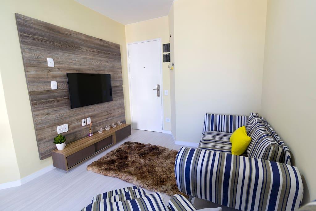 sofá confortável e TV com canais a cabo