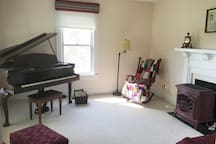The music room features a baby grand piano, a gas-fired stove and a table for games/cards.