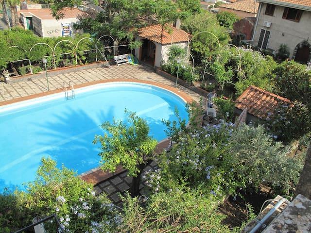 Ampia piscina inserita in un giardino di agrumi: arance, mandarini e pompelmi.