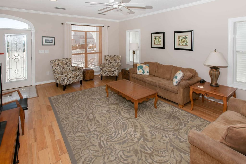 Living room with wood floor, ceiling fan and seating for 7