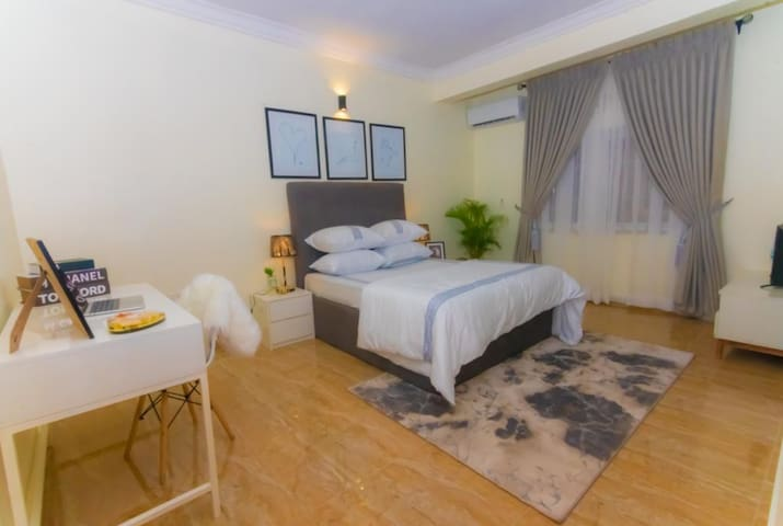 Side view of the spacious second bedroom, with a comfortable work area. The bedroom is furnished with a Queen sized mattress, side stools, lamps, ultra modern wall art, television and television