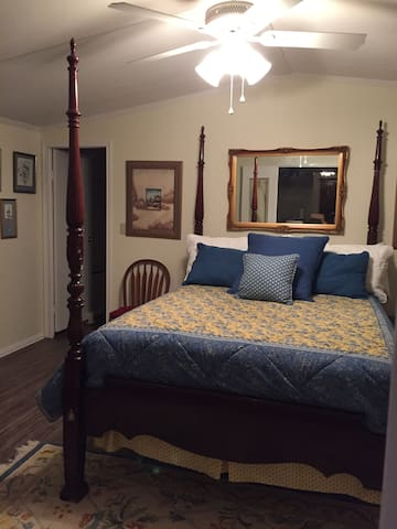 A Master bed room with a queen bed and lots of storage with a walk-in closet and a shower and bath room. Door on the left is bathroom and laundry. Door on the right is closet.