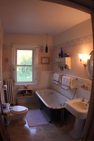 An old time bathroom with a claw foot tub.  A shower handle is attached.