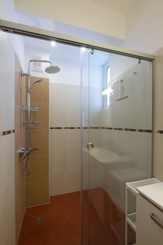 Bathroom has a large, enclosed shower and vanity. Hair dryer immediately outside. Good lighting.