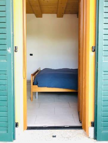 Camera 2 con letto 2 piazze e finestra che porta alla veranda