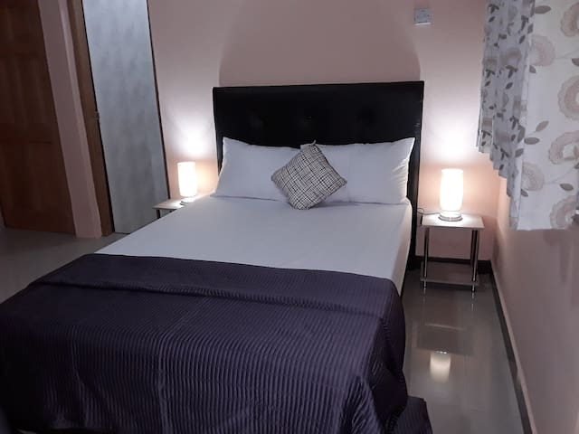 Bedroom 1: Ensuite bedroom fitted with a double bed, wardrobe, air conditioner, ceiling fan, bedside unit and lamp